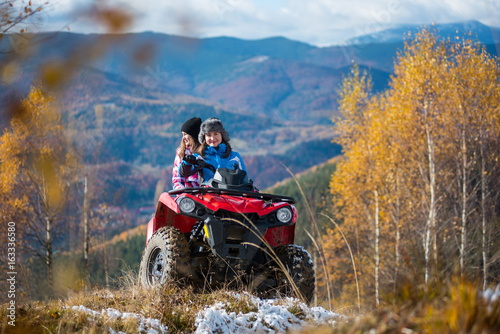 Women riding on ATV in winter clothing on snowy hills on the background of mighty mountains and trees with yellow leaves