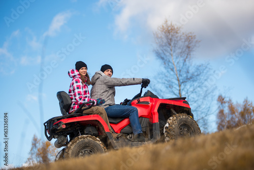 Bottom view couple on the red ATV quad bike against blue sky with blurred background nature. Girl hugging man, they looks at the camera