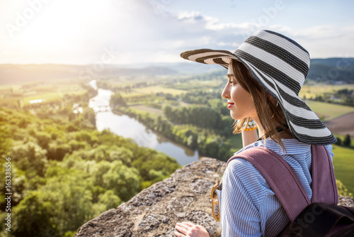Foto  Young woman tourist in hat enjoying sunset view on the beautiful landscape with