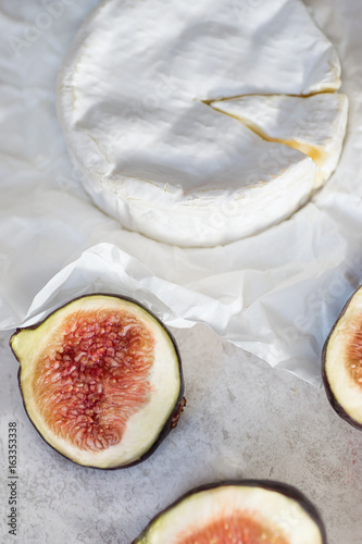 Camembert cheese and fresh figs on a background of craft paper, top view