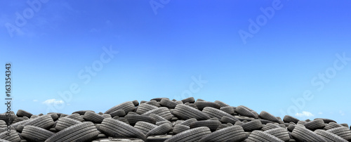 pile of used rubber tires with over light in blue sky background © memorystockphoto
