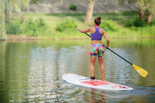 Young Woman On A Board With An Oar. Side View - The Concept Of Harmony With Nature, A Free And Healthy Lifestyle, Supernumerary Staff