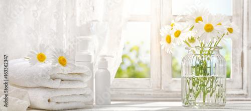 Fotografia  towel with daisy flowers near window