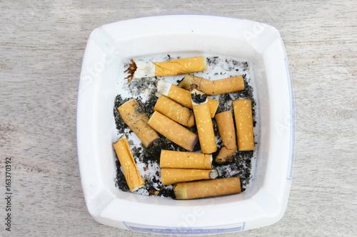 Fotografie, Obraz  mégots de cigarettes dans cendrier,fond bois