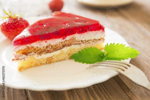 Plakat Truskawka tort z liściem mennica na talerzu na drewnianym stołowym tle