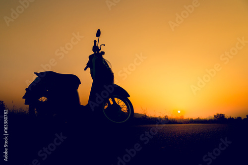 Foto op Canvas Scooter Silhouette scooter standing on field at sunset