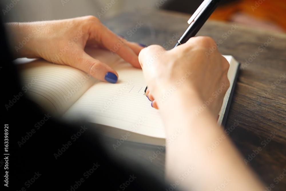 Fototapeta Kalendarz. Kobieta zapisuje w kalendarzu notatkę