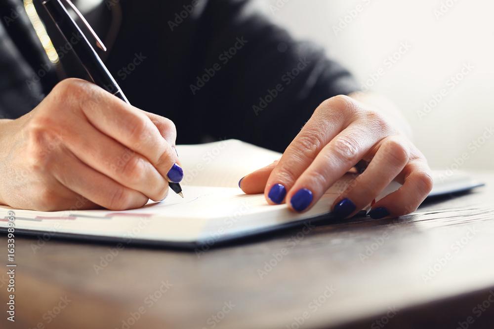 Fototapeta Kalendarz biznesowy. Kobieta zapisuje w kalendarzu notatkę