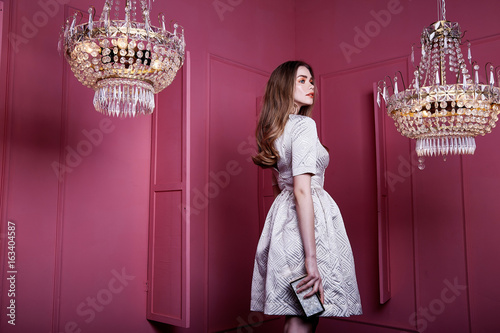 Beautiful sexy pretty face blond hair woman girl lady fashion model wear style clothes office party casual elegant light atlas dress accessory bag interior pink wall room chandelier summer collection.