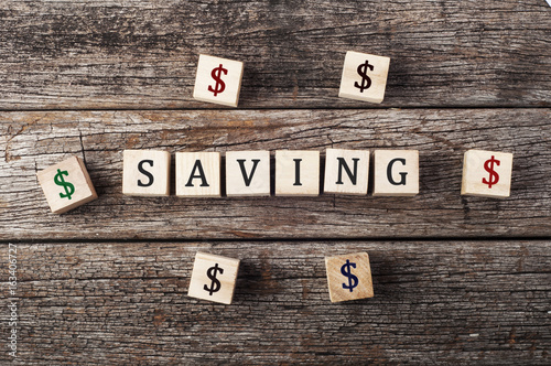 Saving Word On Wood Block With Dollar Symbol Financial Concept