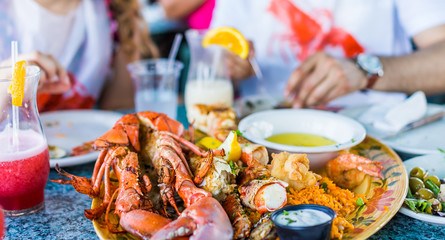 Macro closeup of lobsters and seafood on plate with tartar sauce and garlic b...
