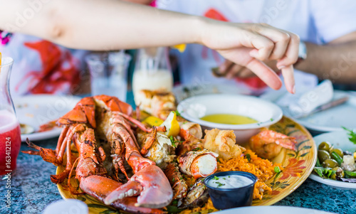 Fototapeta Closeup of lobsters and seafood on plate with hand reaching for garlic butter