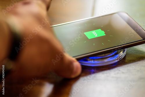 Fotografia  Smartphone charging on a charging pad. Wireless charging