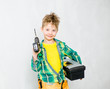 Young boy with tool belt holding drill and toolbox