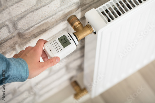Fotografie, Obraz  Person Adjusting Temperature On Thermostat