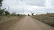 A view of the rural dirt road from camera installed on back of the car driving along this country road. Riding on a rough roadway. High voltage power line pylon.