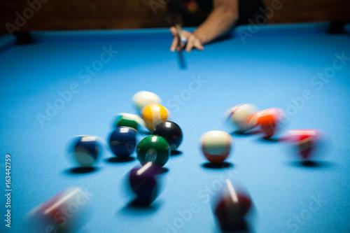 Plakat Niebieski stół bilardowy z kolorowymi kulkami, początek gry, zwolnione tempo, nieostrość, bilard, rozrywka w klubie nocnym, hobby i koncepcja sportowa, strzał akcji bilardowy stół bilardowy i piłki