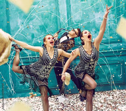 trzy-osoby-tanczace-w-strojach-retro-na-tle-turkusowej-sciany