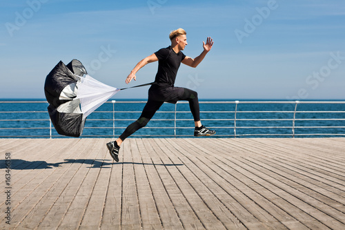 Fotomural  Side shot of man running with parachute