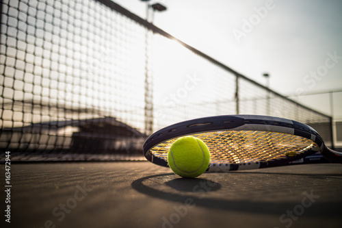 Tennis ball and racket on hard court under sun light