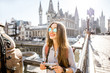 canvas print picture Portrait of a young woman tourist with photo camera traveling in the old town of Gent city during the sunrise in Belgium