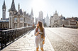 canvas print picture Young woman tourist walking the bridge in the old town of Gent city durnig the sunrise in Belgium