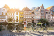canvas print picture Sunrise view on the water channel with beautiful old buildings with woman standing near the bicycles in Gent city