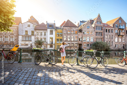 canvas print motiv - rh2010 : Sunrise view on the water channel with beautiful old buildings with woman standing near the bicycles in Gent city