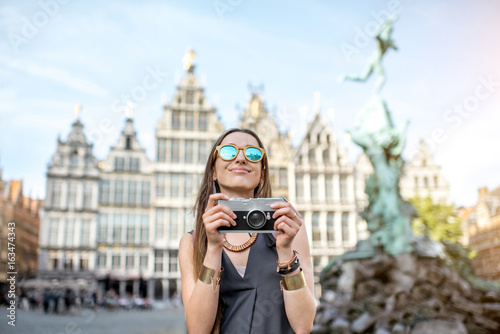 Poster Antwerp Portrait of a young woman tourist with photo camera on the Great Market square in Antwerpen city in Belgium