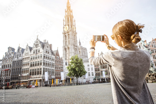 Poster Antwerp Young woman tourist photographing with phone famous cathedral standing on the Great Market square during the morning in Antwerpen, Belgium