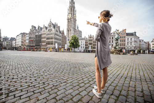 Poster Antwerp Young woman tourist showing with hand famous cathedral tower standing on the Great Market square during the morning in Antwerpen, Belgium