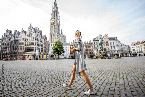 Poster Antwerpen Young woman tourist walking on the Great Market square during the morning in Antwerpen, Belgium