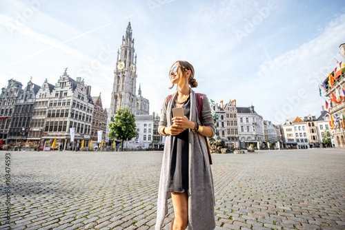 Foto auf AluDibond Antwerpen Young woman tourist walking on the Great Market square during the morning in Antwerpen, Belgium