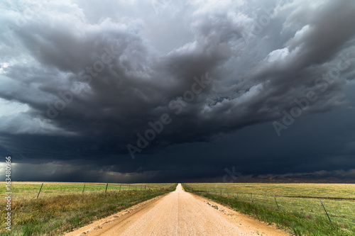Montage in der Fensternische Onweer Dirt road with dark storm clouds