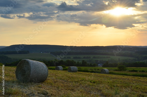 Summer Sunset over hay bales on the farms and hills of upstate New York Wallpaper Mural