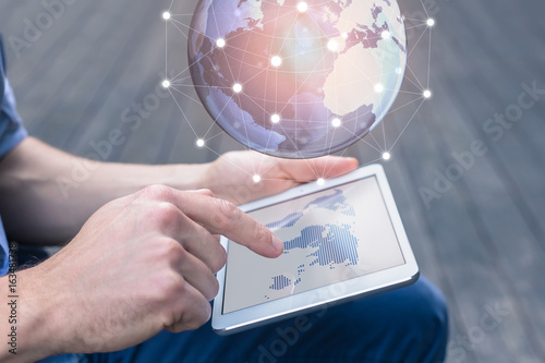 Fotomural World wide business concept, person using AR tablet, 3D globe
