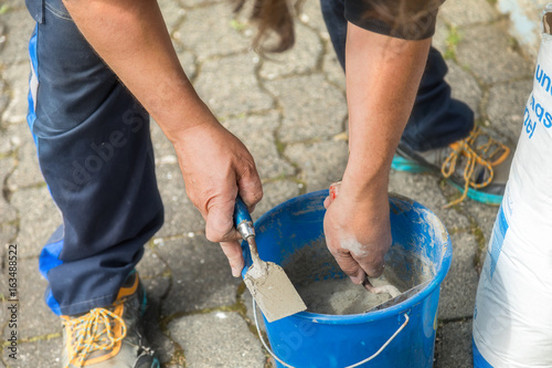 Photo  Two hands with bricklayer trowel, do prepare mortar.