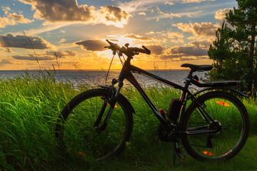 Fototapeta na wymiar Bike by the river in the setting sun. Siberia, Russia