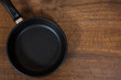 Empty Black Frying Pan on the brown wooden table background. with copy space. top view.