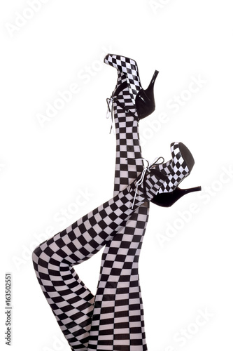 Fotografía  A pair of motorsport legs are stretched out high in a vertical  form in front of a white background
