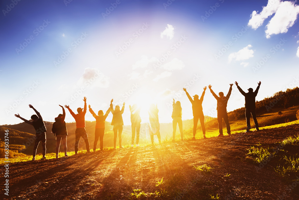 Fototapeta Big group of friends raising arms on sunset together