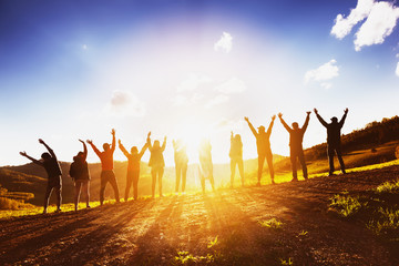 Big group of friends raising arms on sunset together