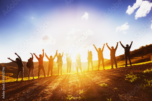 Fototapeta Big group of friends raising arms on sunset together obraz