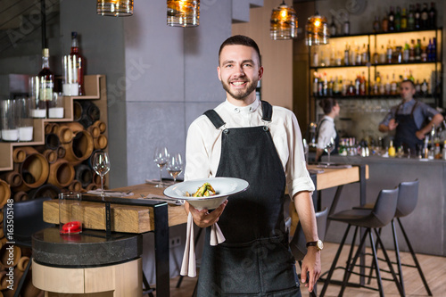 Fotobehang Restaurant A handsome young guy with a beard dressed in an apron standing in a restaurant and holding a white plate with a moth. Against the background, the bar counter and loft style interior