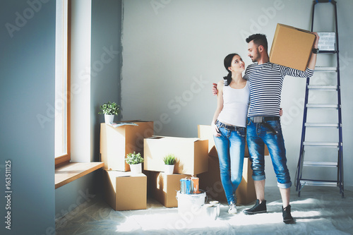 Obraz Happy young couple unpacking or packing boxes and moving into a new home - fototapety do salonu