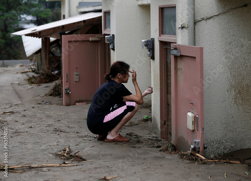A local resident sits in front of mud covered door of her room as