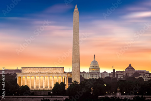 Photo Stands Historical buildings Dawn over Washington - with 3 iconic monuments illuminated at sunrise: Lincoln Memorial, Washington Monument and the Capitol Building.