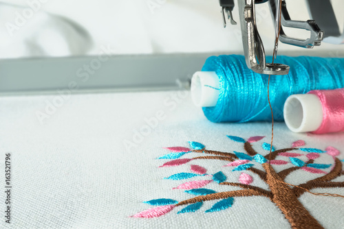 Cuadros en Lienzo Picture of workspace in the embroidery machine close up look under the needle, lovely tree minimal sytle on background have two colorfull thread cyan and pink