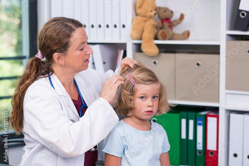 Fotografia  female pediatrician in white lab coat examined little patient for lice