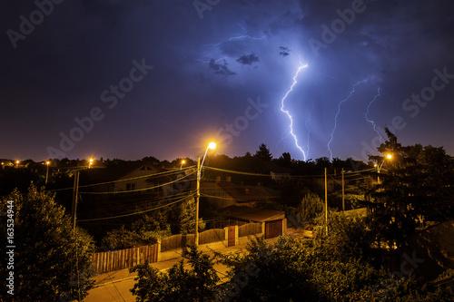 Plakat Grzmot burza nad domami w kraj stronie po środku nocy z piękną błyskawicą w tle